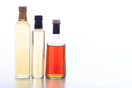 Bottles of vinegar on white background